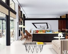 Designer Tino Zervudachi of Mlinaric, Henry & Zervudachi worked with local sources to restore and furnish Nat Rothschild's house in Rio de Janeiro. The glass-top table in the living room is from Firma Casa; the wood Whale lounge chairs are by Julia Krantz. On the wall is a piece by Brazilian artist Regina Silver | archdigest.com