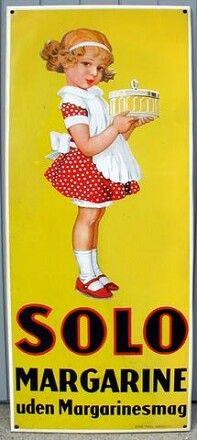 Gul SOLO pige hvor hun kigger til højre. Solo fabrikken lå i Sønderborg, senere omdøbt til ALFA-SOLO a/s, senere igen OMA Otto Mønsted a/s - og i dag UNILEVER. I den tidlige start var margarine et farveløst produkt, lidt henad palmin. Man måtte IKKE fra fabrikkens side farve det gult, da det så kunn...