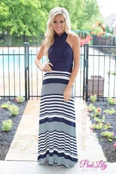 This gorgeous navy and white dress is perfect for any formal occasions! Featuring a variety of widths in the stripes, this dress also has a v-neck and halter top. Additionally, the fabric that forms the halter top and cross-shaped back detail also ties around your waist and cascades down your back. You can even wear it in a variety of ways - check out our images to see this dress as a halter top, v-neckline, and one-shoulder version!