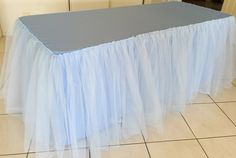 "get plastic tablecloth and tulle in coordinating color, get velcro strips and attach tulle ""skirt"" around table"
