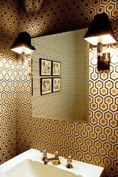 David Hicks paper in gold foil.  Yes!  Lovely paired with the black shades on the sconces.