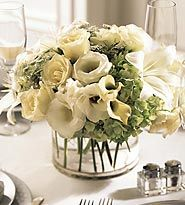oriental lily centerpieces - All white roses, mini callas, spray roses, lilies and double lisianthus are nicely accented by green hydrangea blossoms in a stylish glass cylinder