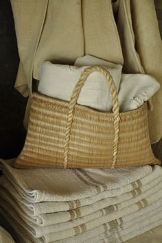 Hand woven rush bag from Hungary filled with vintage linens sat on a stack of Hungarian grain sacks.