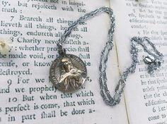 This necklace features a cleaned Vintage* Religious Catholic charm on a shimmering & delicate wave silver chain. Comes ready for gifting in an organza bag.  *Please review carefully all pictures and measurements attached. Note that the pendant is Antique-Used-Old.  ⚓✝✞✟☾  QTY: 1 Necklace Measurements Approx.: Vintage charm 22 mm x 20 mm NEW White silver 1.4mm wave chain : 43cm length © ALIEN SCTY