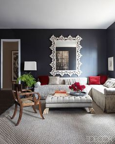 In the living area, Schumacher fabrics cover the sectional, pillows, and chair; the sofa's trim is by Samuel & Sons, the mirror is Indonesian, and the rug is by Patterson, Flynn & Martin. The walls and door frame are painted in Benjamin Moore's Notre Dame and Barely There, respectively.