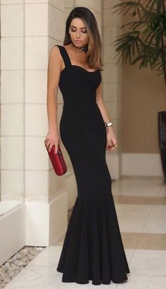 Chic black dress with red clutch.