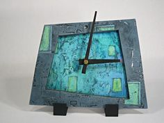 Slate Blue Clock — Eileen Young   Ceramic tiled clock; drawing from her extensive experience with clay and printmaking, Young hand-cuts porcelain and applies a print collage to textured tile surfaces