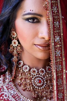"""According to the photographer, the """"colors, culture, and emotion"""" of an Indian wedding inspired this demure portrait of a bride hiding behind an elaborately decorated shawl"""