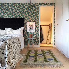 Oryginalna aranżacja sypialni ze wzorzystą tapetą i dodatkami