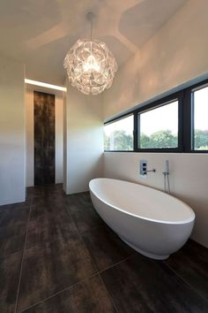Bathroom Tile Idea - Use Large Tiles On The Floor And Walls (18 Pictures) | The large dark tiles in this bathroom allow this bathroom to feel extra lavish, and the continuation of the tile up part of the wall just outside the bathroom makes the space feel connected to the rest of the house.