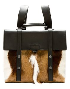 Black Leather and Fur Satchel by 3.1 Phillip Lim. Buffed leather satchel-style backpack. Gunmetal tone hardware. Adjustable leather shoulder straps. Single carry handle. Fur panel at front in tones of cream and brown. Flap and push claps closure at front with two-button press-stud straps. http://zocko.it/LDCBh