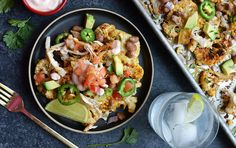 """These are """"na-cho"""" usual chips. This recipe uses roasted cauliflower as the nacho base and is topped with chicken, cheese and beans."""
