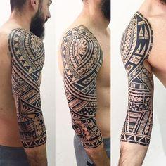 ein junger mann mit grauen hosen und bart und einem großen schwarzen maorie tattoo