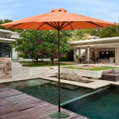 A view from a section of decking to one of the courtyards, showing access to the infinity pool and one of the dining and kitchen areas. A massive tree graces the center of the courtyard.