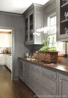 Perfect gray kitchen and butcherblock counters, love the woven metal mesh inserts instead of glass or wood panels.