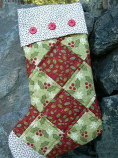 Heres a great stocking for Santa to fill with treats.    This soft mix of regular fabrics and flannel stocking measures 17 in length from cuff to heel and 11 from heel to toe. The back is a matching holly print. A layer of batting in the front and a full muslin lining, plus a flannel print fold-down cuff, add to the strength of this stocking to hold lots of Santas goodies. It is machine stitched and quilted using quality cotton fabrics and batting and trimmed with three red shaped buttons…
