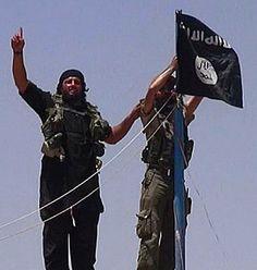 10 mars 2015 - Le groupe Etat islamique a décapité en public deux hommes accusés d'homosexualité et un autre de blasphème, dans le nord de l'Irak, selon des photos diffusées mardi sur les réseaux sociaux. (Sur la photo: Des militants de l'État Islamique installent leur drapeau sur une route entre la Syrie et l'Irak dont ils ont pris le contrôle.)