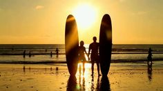 Surfer couple in silhouette holding long surf boards at sunset on tropical beach - HD stock video clip