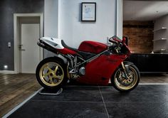 Classic 998 faired bike with Ducati picked out in carbon. Front and rear number boards with gold piping and black belly pan.