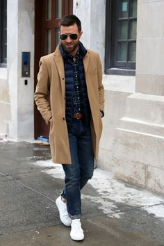 Camel coat + navy down vest + plaid button up + jeans + white sneakers