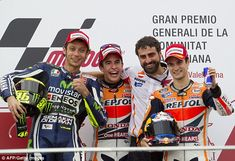 Marquez  celebrates on the podium with his chief mechanic  Santiago Hernandez, with Rossi (left) and Dani Pedrosa completing the top three in the final race of the MotoGP season