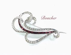 """A beautiful Brooch stamped Boucher Patent Pending 23??, Is shaped in a smooth free flowing wave form. Clear rhinestones and deep burgundy red make this luxurious looking. Excellent brooch for the holidays and an amazing 4"""" long x 1.5"""". Features Rhodium plating and smooth construction. In great condition, missing a few clear stones, easy fix. Please look at pictures. A lovely vintage piece of signed Marcel Boucher to collect. Also there is a name engraved on the back """"bub cabt"""" 