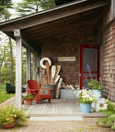 Simple enamel buckets make for cachepots with laid-back charm, while the exposed canoe paddles and firewood add to the rustic atmosphere of this lake home in Massachusetts.