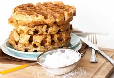 A side view of flax seed Belgian waffles with a sifter full of white powdered sugar.