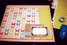two sheets of cardstock: one 12×12 for the background and one cut smaller to mat the two patterned paper boxes in the centre of the page. That full area in the middle pieces together to be 11.5 inches wide and 10.5 inches tall. Then a gathering of patterned paper scraps, a journaling card and some washi tape forms the start to the embellishment.