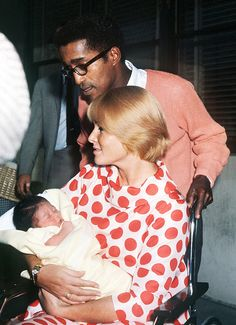 Sammy Davis, Jr. and wife May Britt leave the hospital with their newborn daughter Tracey, 1961.