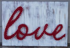 """Etsy shop, AsULikeIt: Mixed Media Nail and Thread """"love""""- 17"""" x 12"""" hand nailed mixed media piece. Background is stained and white washed wood. The piece is hand strung with red thread."""