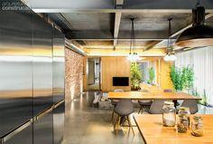 Reforma em oficina de moto cria casa espaçosa na Espanha - Sem acabamento até a sala, a laje sobre a cozinha e o resto da área social integrada foi apenas pintada de cinza. Projeto de Egue Y Seta.