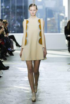 Mini vestido de línea evasé con cuello tirilla, detalles de pestañas circulares en laterales insertadas y mangas de copa elevada elaborado en lana.