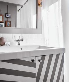 Easy DIY: This white bathroom cabinet gets its stripes from gaffer's tape.