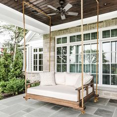 classic front porch idea wood swinging daybed white throw pillows white mattress stone paving floors dark finished wood ceilings ceiling fan of Add A Comfort Zone in Your Front Porch with These Fabulous Front Porch Seating Ideas