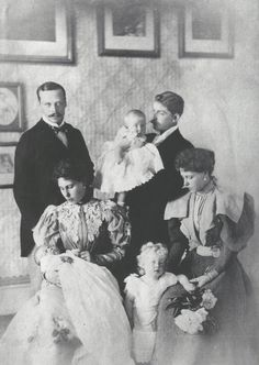 Baby Princess Elisabeth of Hesse in her mother's arms. Behind them, Grand Duke Ernst Ludwig. On the Duke's right, Prince Ferdinand of Romania with his daughter Elisabeta. In front of them, Princess...