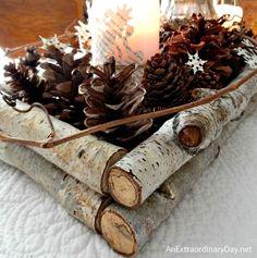 Le centre de table parfait pour Noël. À faire soi-même avec, au centre, une bougie, entourée de branches et de pommes de pin :