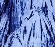 """This is a fragment of a Japanese indigo-dyed shibori textile. Shibori is a resist dyeing method that involved either binding, stitching, folding, compressing, capping, or twisting the fabric to create the tie-dye pattern. Shibori is an example of radial balance, because """"all elements of the design radiate from a central point"""" (Allen & Jones, pg. 105). Image Source: Gunner, """"Shibori for Textile Artists,"""" pg. 12."""