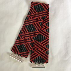 """A wonderful Peyote (Gourd) stitch bracelet in a geometric design using Black, Gray and Red colored Miyuki Delica beads. 1"""" wide and 7"""" long with a 3 ring Sterling Silver tube clasp. All the Peyote bra                                                                                                                                                     More"""