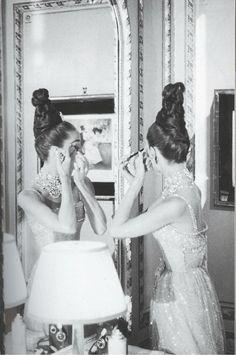 Audrey Hepburn fixing hermakeupin the 1960s.