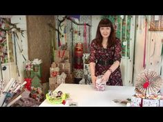 How to wrap a round present using tissue paper, ribbon and a gift topper. Lauren, our wrapping expert, shows you how to wrap a round box using a simple and e...