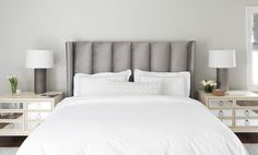 Chic bedroom features a gray velvet art deco wingback headboard on bed dressed in white and gray bedding flanked by cream dressers with mirrored drawers doubling as nightstands and metal column lamps.