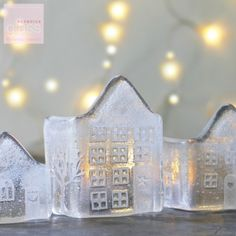 A set of three magical little handmade fused glass houses which look lovely with a tea light candle placed behind. The candle light flickers through the windows to create a festive glow. They can be placed by a window to allow the sunlight to shine through. The houses are all different and have embossed doors, windows and trees on three side and comes with a small glass plate to place your tea light. 11cm by 6cm, 8cm by 6cm, 6.5cm by 6cm,