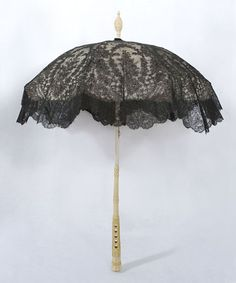 Chantilly lace parasol with carved ivory handle, 1860s, combination of two silk linings. The top lining layer, under the lace, is ivory silk taffeta. The under layer, slightly smaller so it won't show from the outside, is a pink hue. high relief carving of the ivory handle and finial