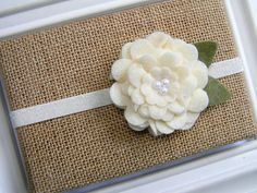 A beautiful, ivory felt flower on an ivory non-flaking glitter elastic headband. The flower measures approximately 2.5. All sizes are estimates for