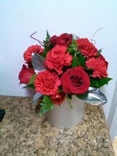 Red roses and red carnations arranged with silver for New Year's!
