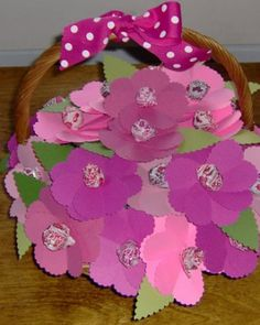 Lollipop Flower Basket  This clever Valentine display comes from CuteStuffInside. She created paper flowers using a scalloped heart punch and scalloped scissors wrote the names of her daughter's classmates on the underside of each leaf. To complete the presentation, she pierced each with a lollipop and arranged them in a basket fitted with a Styrofoam block.