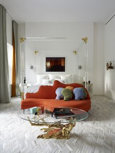 Bedroom Bliss. Wall-to-wall white hide carpet, white walls, a lucite and gold bed, and a vermilion silhouette sofa. Saffron stripe on the leading edge. Interior Designer: Jonathan Adler.
