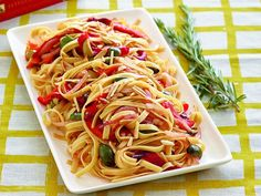 A colourful dish of fettuccine contains slivered red peppers, olives and almonds.
