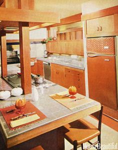 The center island, with lighting and a vent fan built in over the cooking unit, also serves as a work table and desk. Note the space above the cabinets over the sink through which, when the draperies in the passage are drawn aside, one can see the garden beyond. Featured in the February 1962 issue.   - HouseBeautiful.com